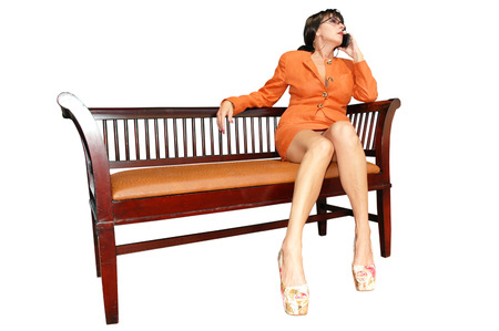 leggy brunette business woman sitting on bench and talking on cell phone