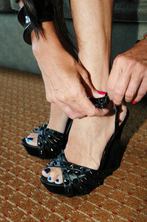 woman fastening buckles on high heeled shoes
