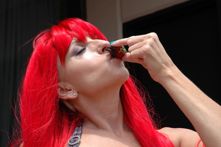 redheaded woman eating chocolate covered strawberry
