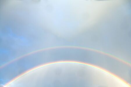 Landscape View of Rainbow twin on the blue sky white clouds background on rainy day