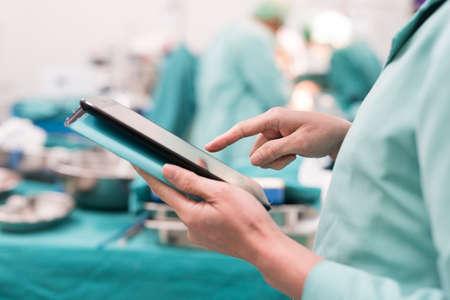 chirurg met behulp van digitale tablet in de operatiekamer Stockfoto