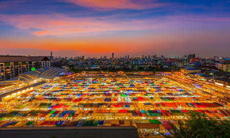 Sunset over Bangkok city business downtown and train night market Ratchada