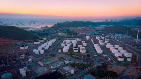 Aerial view oil and gas industrial, Refinery factory oil storage tank and pipeline steel at twilight