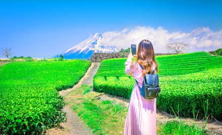 Woman tourists photographing a tea plantation with Mount Fuji