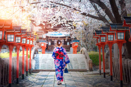 Back view of asia woman with kimono and Japanese umbrella against sakura flower background Foto de archivo