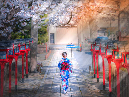 Back view of asia woman with kimono and Japanese umbrella against sakura flower background 写真素材
