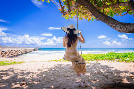 Back view of happy woman relax on swing on beautiful paradises beach at Phang-nga province,Thailand