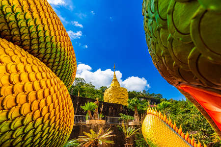 Big gold buddha and naga statue in Wat tham pha daen temple, the famous place of Sakon Nakhon Province, Thailand