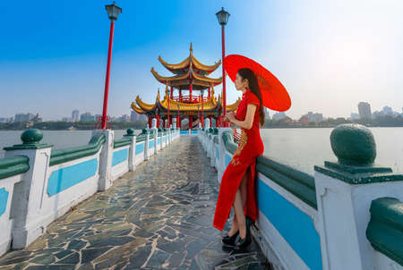 Beautiful Asian Chinese Woman Wearing Cheongsam Traditional Red Dress standing on bridge at Wuliting pavilion,Kaohsiung,Taiwan Stock Photo