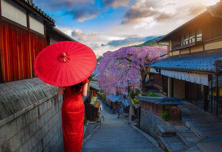 Young women in beautiful  Cheongsam Traditional Red  dress enjoying Historic Higashiyama district, Kyoto in Japan