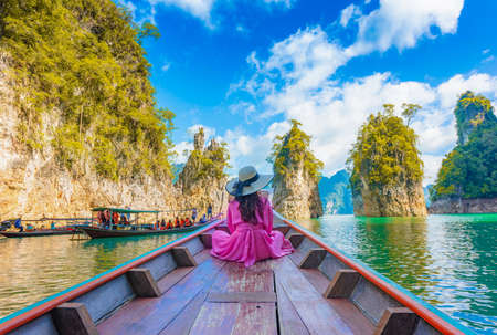 Asian woman sitting on boat in Ratchaprapha dam Khao sok national park at suratthani,Thailand