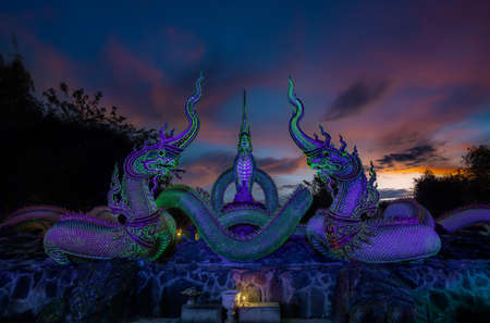 A glowing serpent statue with Twilight at Wat Pa Phupang temple Si Chiang Mai District, Ubon Ratchathani Province, Thailand Imagens