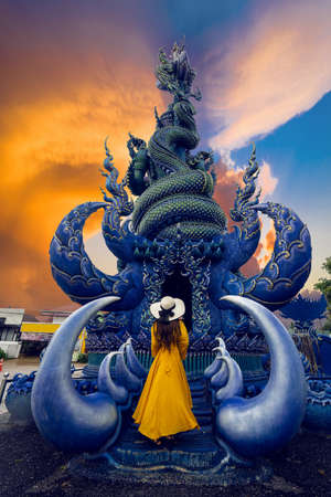 Asian tourists stand to admire a blue statue in a temple in Chiang Rai, Thailand