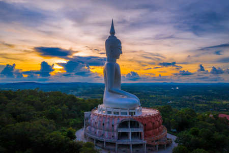 Top view Aerial photo from flying drone.Sunset at  Big Buddha Wat Phu Manorom Mukdahan province, Thailand