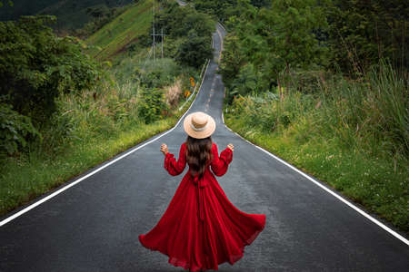 Asian woman walking on Beautiful sky road over the top of mountain and green forest in Pua, Nan province, Thailand