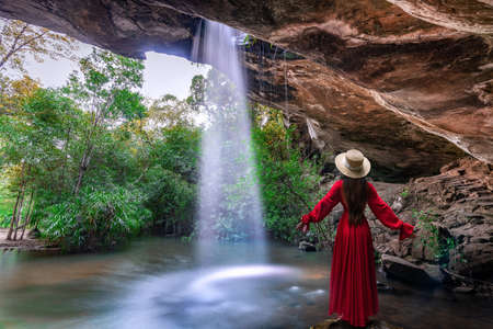 Asian woman standing on the rock at Saeng Chan Waterfall (Long Ru Waterfall), Ubon Ratchathani Province, Thailand.The stone holes are caused by water erosion due to sandstone being less resistant to corrosion