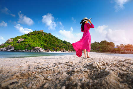 Asian woman walking on the beach of separated sea on the island of Koh nangyuan in Thailand