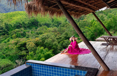 Woman in a pink dress sits at the resort balcony looking at the rice fields at  Sapan village, Nan Province, Thailand Stok Fotoğraf