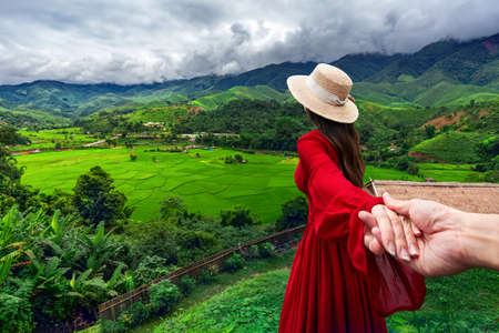 Asian woman wearing a white hat and a red dress stands to admire the beauty of Ban Sa Pan rice fields in Nan Province, Thailand Stok Fotoğraf