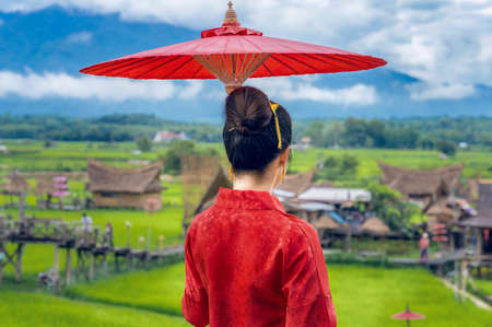 Behind a Thai woman dressed in Thai costumes stands holding an umbrella to see popular tourist attractions in Nan Province, Thailand. Stok Fotoğraf