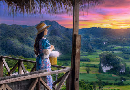Woman wearing blue dress stand and see the mountain view in the morning at phu langka national park,Phayao province, thailand