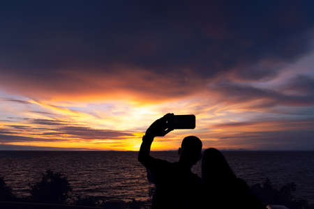 A silhouette of a young couple taking a picture with the sunset at Noen Nang Phaya viewpoint in Chanthaburi, Thailand Stok Fotoğraf