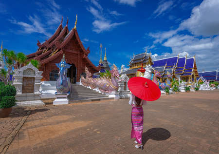 Woman with red traditional Thai umbrella visit ban den temple in Chiang Mai, Thailand Stok Fotoğraf