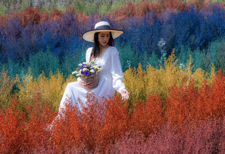Beautiful Thai woman sits among the cutters flower in rainbow colors in Chiang Mai province, Thailand