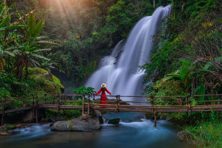 A young Asian tourist wearing a red dress stands on a bamboo bridge watching Pha Dok Siew Waterfall at Doi Inthanon National Park, Chiang Mai Province, Thailand.