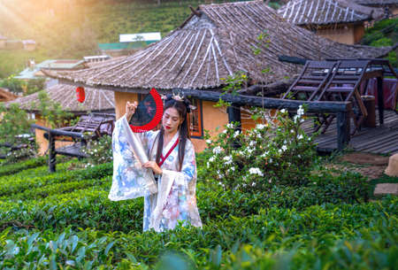 Asian woman wearing a Chinese national costume poses for a photo at a tea plantation in Rak Thai Village, Mae Hong Son Province, Thailand