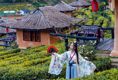 Asian woman wearing a Chinese national costume poses for a photo at  tea plantation in Rak Thai Village, Mae Hong Son Province, Thailand Stok Fotoğraf
