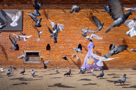 Asian woman tourist walks through the middle of a pigeon next to Tha Phae Gate in Chiang Mai, Thailand