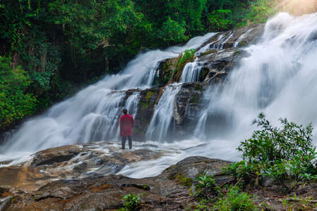 Asian man tourist watching Pha Dok Siew Waterfall at Doi Inthanon National Park, Chiang Mai Province, Thailand.