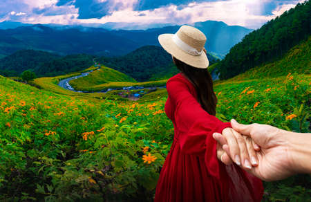 Asian female tourists stand holding hands to admire Dok Bua Tong flower in Mae Hong Son Province, Thailand Stok Fotoğraf