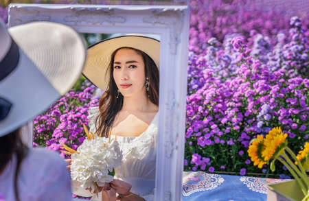 Beautiful woman looking in a mirror in a flower field in Chiang Mai, Thailand