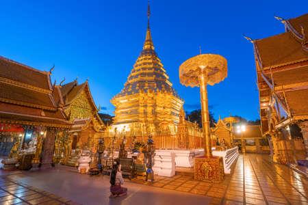 Thai woman wearing a Thai Lana dress sits and prays at Wat Phra That Doi Suthep in Chiang Mai, Thailand Stok Fotoğraf