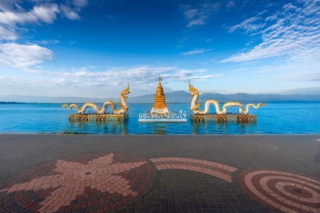 """Naga statue with bright sky, clouds, mountains background and fresh water lake (Kwan Phayao, one of Phayao famous attractions.) in Phayao, Thailand (Thai Language translate """"Happiness Phayao"""" )"""
