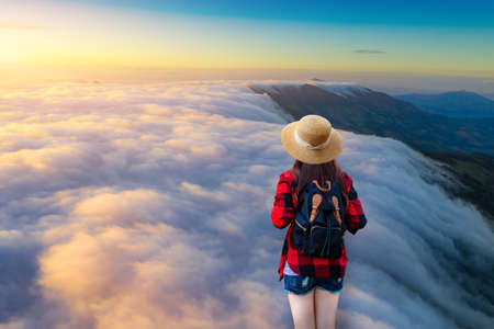 Traveler girl hiker wear hat with backpack looking beautiful nature,fogy landscape on high mountain at viewpoint of Phu Chi Fa Forest Park during sunrise in Chiang Rai Province Thailand