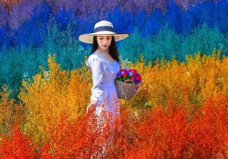 Beautiful Thai woman stangding among the cutters flower in rainbow colors in Chiang Mai province, Thailand