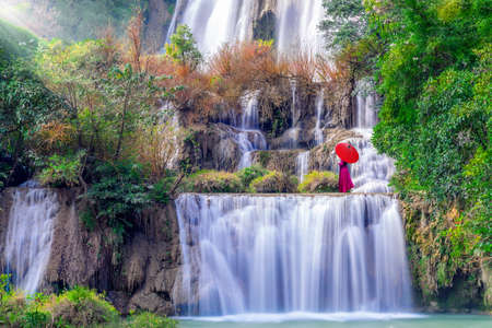Asian woman standing at Tee lor su waterfall in Thailand. at the tropical forest , Umphang District, Tak Province, Thailand Banco de Imagens