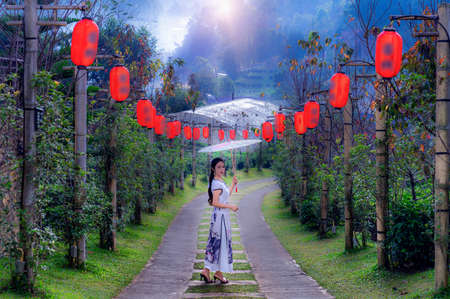 Asian woman wearing a Chinese national costume poses for a photo at  tea plantation in Rak Thai Village, Mae Hong Son Province, Thailand Imagens