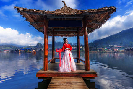 Asian female tourist stands on the water hall at Ban Rak Thai, Mae Hong Son Province, Thailand Imagens