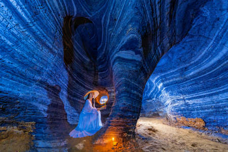 Asian woman in a white dress visits a blue cave in Tak Province, Thailand