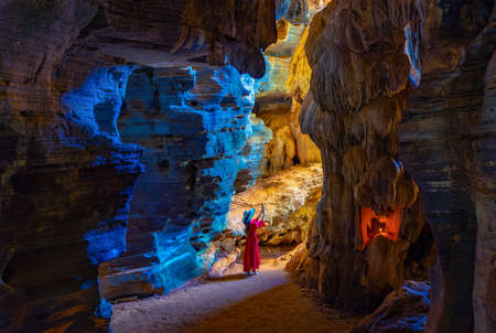 Asian woman in a pink dress visits a blue cave in Tak Province, Thailand Imagens