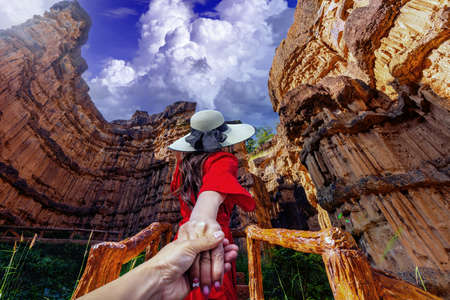 Asian female tourists stand and watch cliff stone of Pha Chor at Mae Wang National parks in Chiang Mai,Thailand