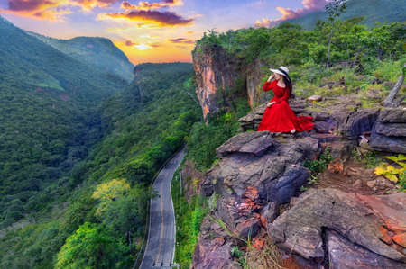 Thai woman in red dress sitting on the rock at Pha luang daeng viewpoint, Chiang mai, Thailand