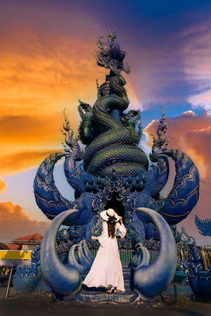 Asian woman tourists stand to admire a blue statue in a temple in Chiang Rai, Thailand