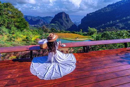 Thai girl wearing a white dress looking at Phahee Viewpoint, Mae Sai District, Chiang Rai Province, Thailand Imagens