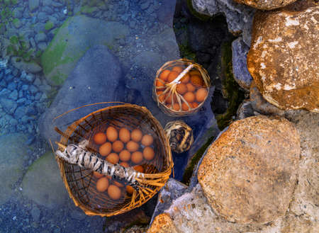 Bamboo baskets contain many eggs and are immersed in a hot spring at Chae Son National Park, Lampang province, Thailand Imagens