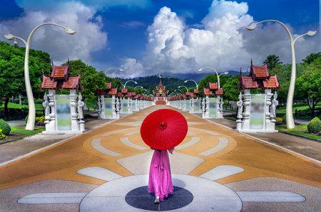 Thai woman with  umbrella walks to see Ho Kham Luang Pavilion at Royal Park Rajapruek in Chiang Mai, Thailand